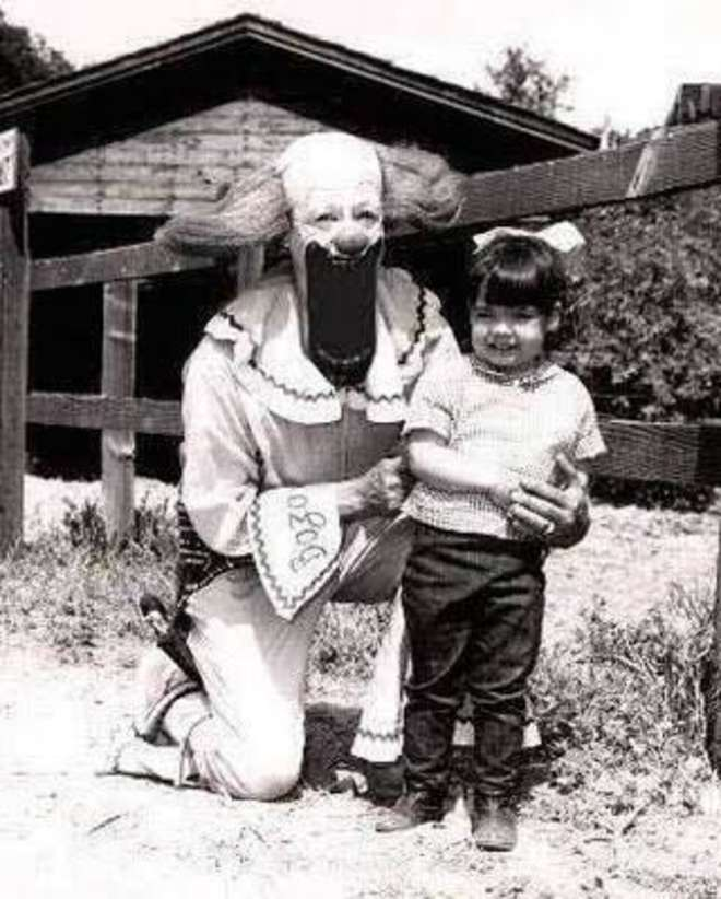 A Photo Of A Man Dressed As A Creepy Clown With A Small Girl - 10 Eerie Photos That Will Send Shivers Down Your Spine