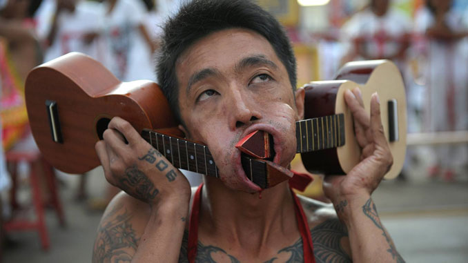 Man with guitars through his cheeks at the Vegetarian Festival in Thailand - 10 Most Insane Body Modifications You Just Have To See