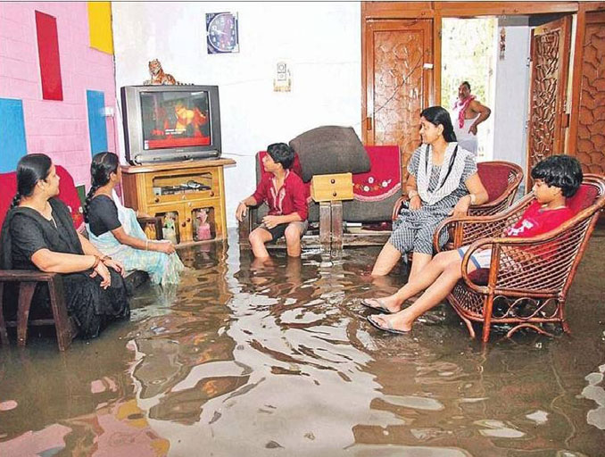 Indian family watching T.V. during a flood - 20 WTF Photos You Just Have To See