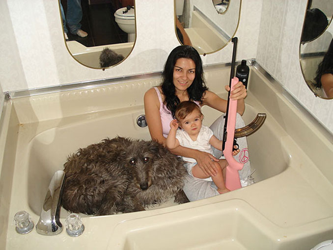 Family in a bathtub with a dog and a pink gun - 20 WTF Photos You Just Have To See