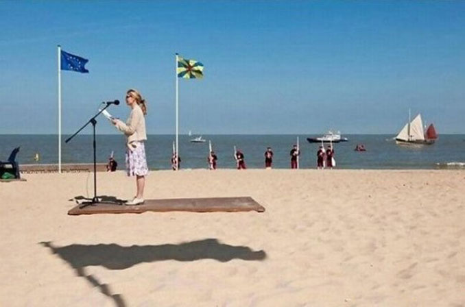 A woman giving a speech at the beach that looks like the podium is hovering.