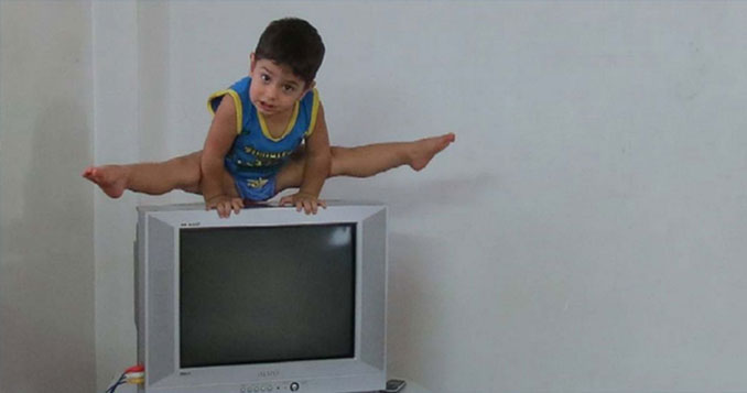 Arat Hosseini doing the splits on a T.V.