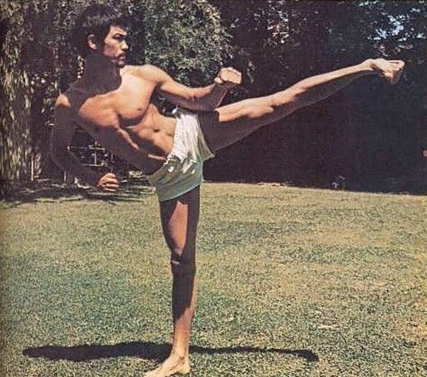 Bruce Lee performing a side kick.