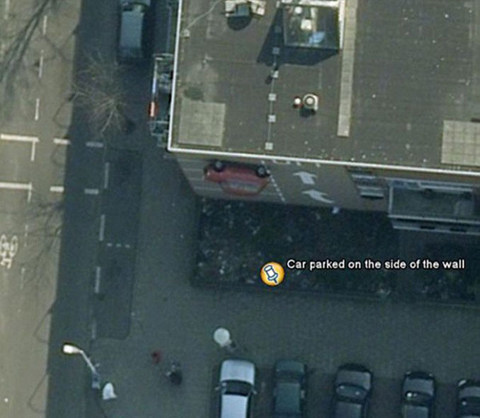 A car parked on the side of a building seen on Google Earth.