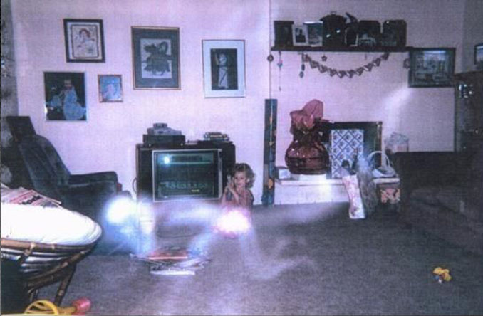 A photo of a ghost kneeling on all fours in front of a young girl.