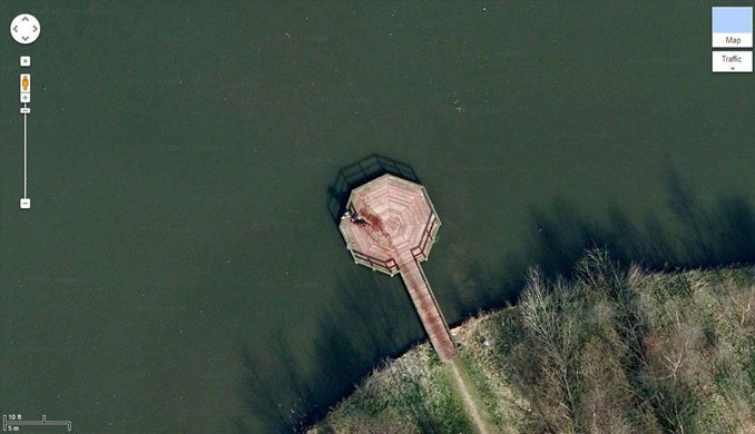 An aerial view that looks to show two people dragging a dead body on a pier seen on google Earth.